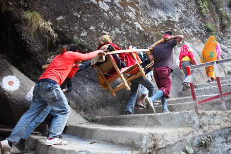 A woman devotee carried in a palanquin to Yamunotri temple Uttarkashi Uttarakhand India Asia Stock Photo