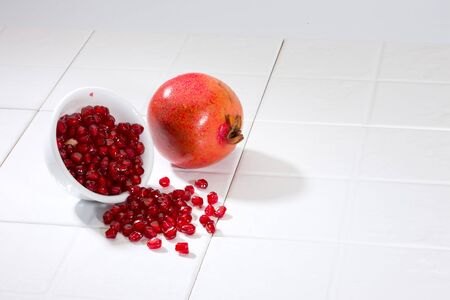 Pomegranate with seeds in bowl