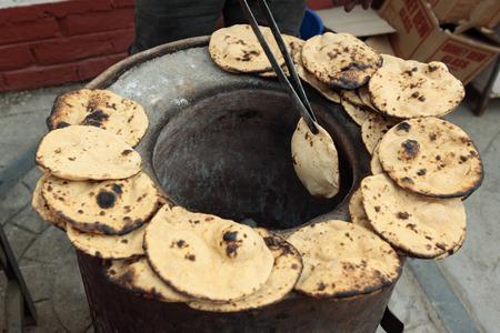 Indian Bread Tandoori Roti baking in Tandoor oven India