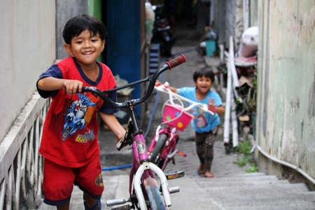 babysitting: Happy and smiling children playing with their bycicles. Daily life scene from the streets of South Yogyakarta