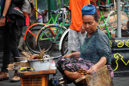blighted: YOGYAKARTAINDONESIA - NOVEMBER 2015: A lady selling street food in Malioboro Street, the most centric and touristic road of Yogyakarta.