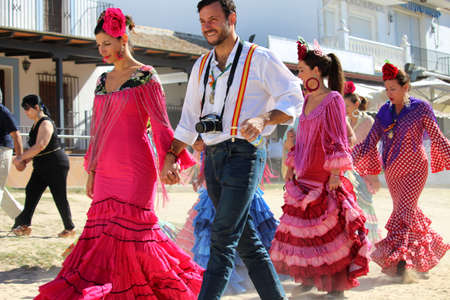 HUELVA  SPAIN - OCTOBER 9 2016: Piligrims in colorful dresses going to the sunday holy mass at the shrine of El Rocio