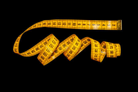 Yellow measuring tape isolated on a black background. Stockfoto