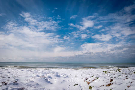 Unusual snow covers the sand of Naples beach, extraordinary snowfall on the coast of Naples, Italy - Climate Change concept