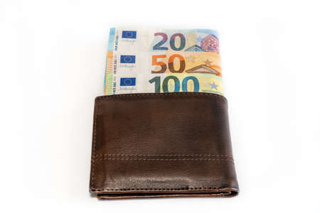 Top view of brown genuine leather wallet with banknotes inside isolated on white background.