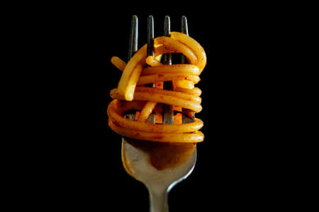 Close up of Italian Spaghetti on a fork with tomato sauce on black background. Typical Italian Food, stereotype to identify Italian culture. High quality photo