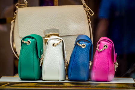 Featured colorful leather womens handbags in the store. Shopping concept