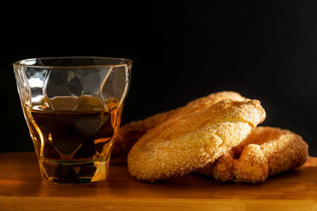 Close up of sweet donuts with sugar and a glass of rum on wooden board and black background