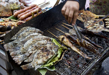 grilled salty fishs tilapia,catfish  in wheelbarrel on street of Bangkok  ,Thailand photo