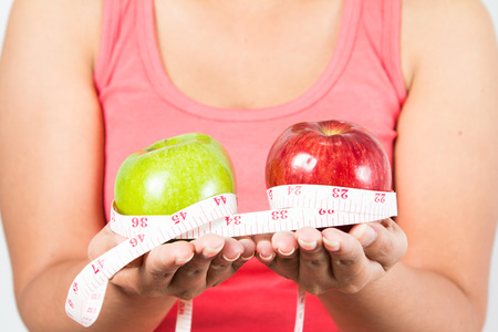 asian woman measuring waist as she holds apple in fitness studio photo