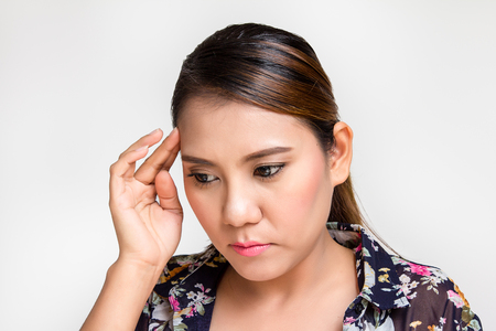 Asian woman with headache touching her temples