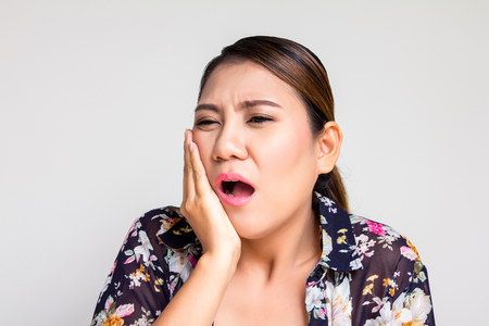 dolor de muelas: Beautiful asian woman suffering from toothache on white background