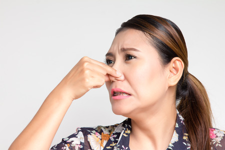Asian woman closing her nose