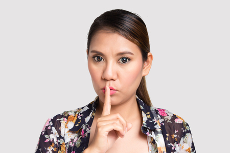 restraint: Asian woman doing silence sign against on white background Stock Photo