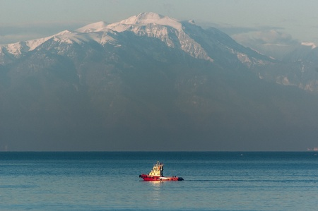 A red tugboat sailing in the sea with snowy Mt Olympus, highest mountain, as a background Editorial
