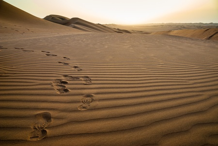Footprints on the sand at sunrise in the desert of Ramlat al-Sab Stock Photo