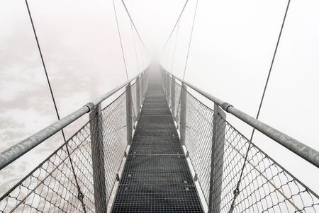 A metallic bridge for hikers in snowy Austrian Alps during a foggy day