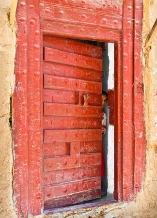 Al Hajarayn, Yemen - May 8, 2007: An unidentified girl looks through the half-open door of her house