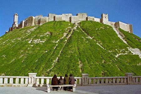 Aleppo, Syrië - 15 maart 2004: Een groep van drie niet-geïdentificeerde vrouwen en een meisje, gekleed in het zwart, geniet van het uitzicht op de Citadel van Aleppo, een UNESCO World Heritage Site en een van de oudste en grootste kastelen in de wereld Redactioneel