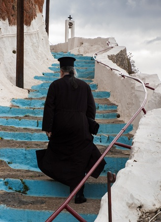 Peloponnese, Greece - October 11, 2005: An unidentified Greek-Orthodox priest climbs a stair