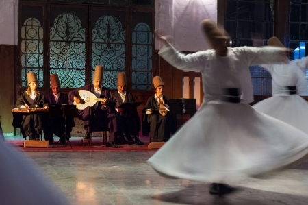 Istanbul, Turkey - October 21, 2005: Whirling dervishes and musicians perform to visitors in the event hall of Sirkeci Train Station, the old terminus of the Orient Express