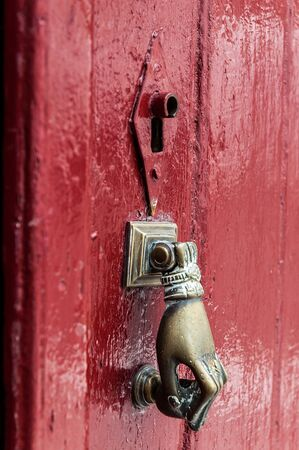 Knocker on old red door in Greece photo