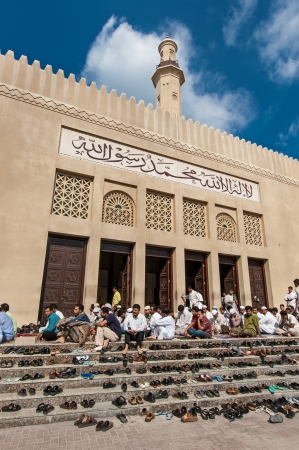 Dubai, UAE - December 31, 2004: A number of unidentified men wait outside the Grand Mosque for the midday prayer.