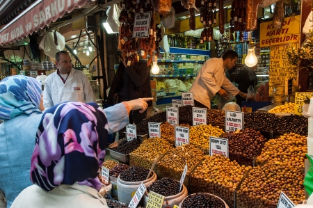 Istanbul, Turkey - October 25, 2005: Two unidentified women with traditional colorful kerchiefs buy olives from Fatih Market.