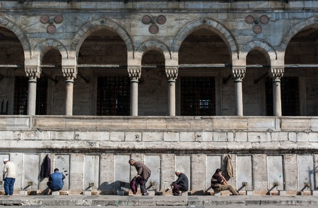 Istanbul, Turkey - October 26, 2005: A number of unidentified men wash themselves before entering the Sultan Ahmed Mosque for prayer
