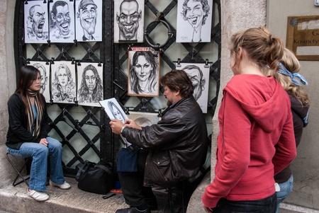 humoristic: Cracovia, Polonia - 25 de octubre de 2006: Un artista hace retratos humor�sticos de turistas. Cracovia es un centro tur�stico importante debido a su fina arquitectura, la cultura y la historia bien conservado.