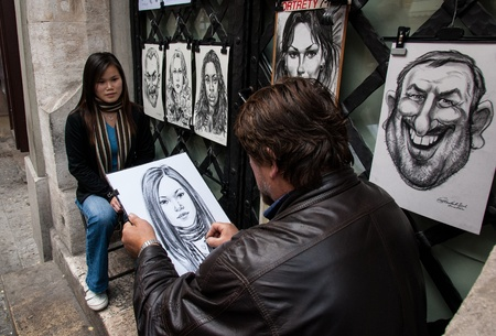 Krakow, Poland - October 25, 2006: An artist makes humoristic portraits of tourists. Krakow is a major tourist centre because of its fine architecture, culture and well preserved history.