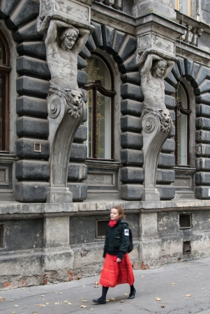 Krakow, Poland - October 25, 2006: A young woman walks by an old building, decorated with statues. Stock Photo - 17298377