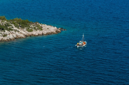 promontory: Traditional fishing boat near a promontory in Greece