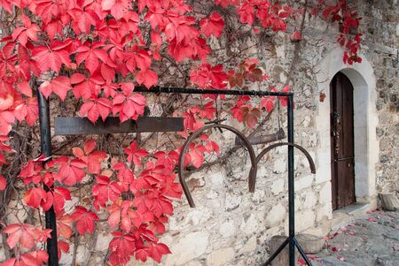 Traditional iron semantron - i.e. kind of bell in Greek Orthodox monasteries - with red leaves in Greece photo