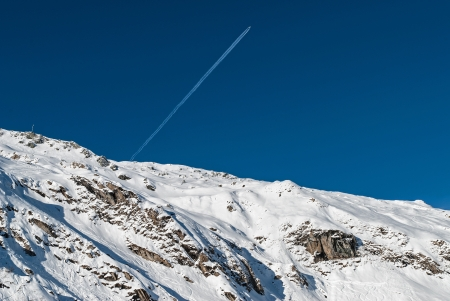 Airplane over snowy mountain in Austrian Alps