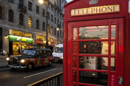 London, UK - April 10, 2007: Red telephone box and black cab Редакционное