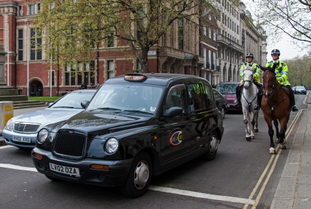 London, UK - April 13, 2007: Black cab and mounted police officers