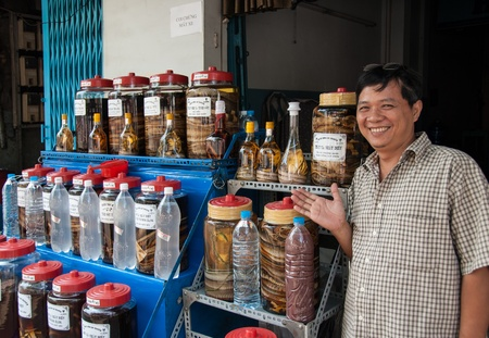 infusing: Ho Chi Minh City, Vietnam - February 14, 2007: A man sells snake wine. Snake wine is a traditional alcoholic beverage produced by infusing whole snakes in rice wine. Editorial