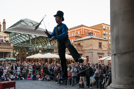 London, UK - April 1, 2007: A juggler performs in Covent Garden. Covent Garden, one of the main attractions in London, is known for everyday street performance through the whole year. Редакционное