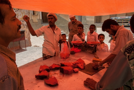 suq: Al Hajarayn, Yemen - May 8, 2007: A man sells fish in an open market. Due to the rich with fish species Red Sea, fish markets play a central role in the economic life of Yemen.