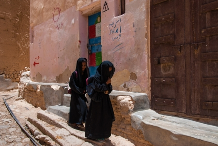 burqa: Al Hajarayn, Yemen - May 4, 2007: Two girls return from school. Although infant mortality is high, children in Yemen are culturally, socially and religiously valued.