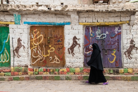 burqa: Ibb, Yemen - May 10, 2007: A woman walks in the street. Modern day women of Yemen do not hold many economic, social or cultural rights.  Editorial