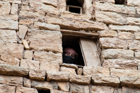 Thula, Yemen - May 5, 2007: A woman looks through her window. Modern day women of Yemen do not hold many economic, social or cultural rights.