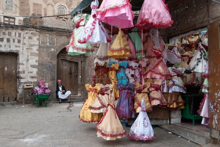 Sanaa, Yemen - May 4, 2007: A man sells colorful dresses for girls. Although infant mortality is high, children in Yemen are culturally, socially and religiously valued.