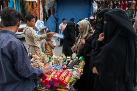 burqa: Sanaa, Yemen - May 4, 2007: A group of women buy biscuits. Open markets play a central role in the social-economic life of Yemen, one of the poorest countries in the Arab World.