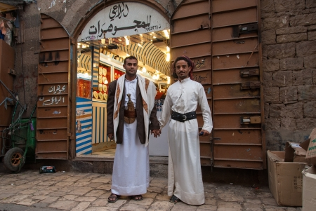 suq: Sanaa, Yemen - May 4, 2007: Two men pose hand in hand in front of a jewellery store. Among other arabic countries, in 2012 Yemen became a site of civil conflicts. Editorial