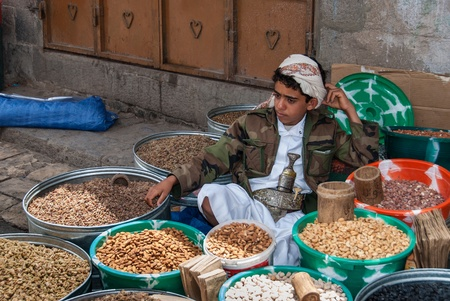suq: Sanaa, Yemen - May 4, 2007: A boy sells dried fruits. Open markets play a central role in the social-economic life of Yemen, one of the poorest countries in the Arab World.