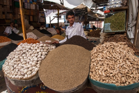 suq: Sanaa, Yemen - May 4, 2007: A man sells spices. Open markets play a central role in the social-economic life of Yemen, one of the poorest countries in the Arab World.