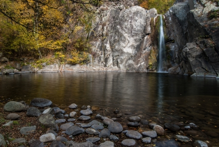 Waterfall and small lake in a mountain forest in Autumn Stock Photo