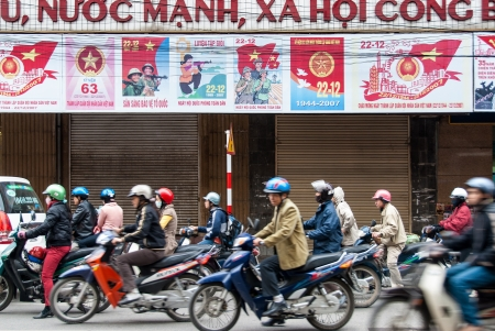 Hanoi, Vietnam - January 14, 2008: Unidentified men and women drive their motorcycles. Being several millions, these two-wheeled vehicles are the preferred method of transport around Hanoi. Редакционное